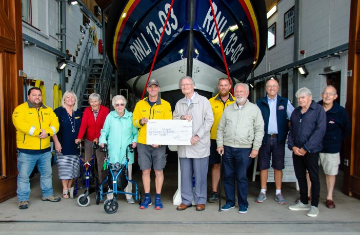 Residents of Manor Lodge Residential Care Home present a cheque to Exmouth RNLI coxswain Steve Hockings-Thompson at the lifeboat station flanked by other volunteer crew members and staff. Picture: John Thorogood / Exmouth RNLI