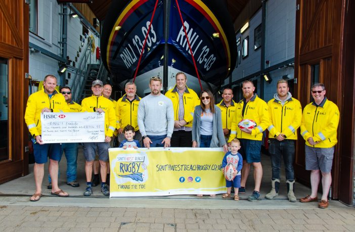 Holding the cheque (l-r) are Roy Stott, Exmouth RNLI deputy coxswain; Steve Hockings-Thompson, Exmouth RNLI coxswain. Holding the banner in front of Exmouth RNLI crew members are Matt and Sarah Jess and their two boys Ted and Alfie. Picture: John Thorogood