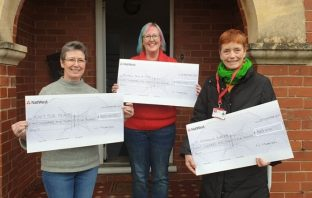 Natalie Morrison (centre), of Exmouth, handed over £825 to St Petrock's, Knit for Peace and her own Rainbow Arch of Mind.