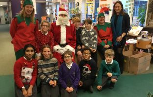 Pupils and staff from St Sidwell's Primary School in Exeter celebrating winning the Leg it to Lapland challenge with a visit from Santa and his elves.