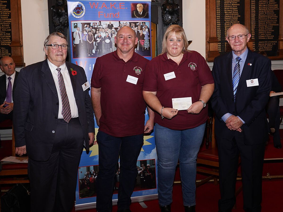 Emma and Paul Baldwin,  of Exmouth Gateway Club, receiving a cheque from Ian Kingsbury accompanied by W.Bro. David Bassett from The Sun Lodge No 489.