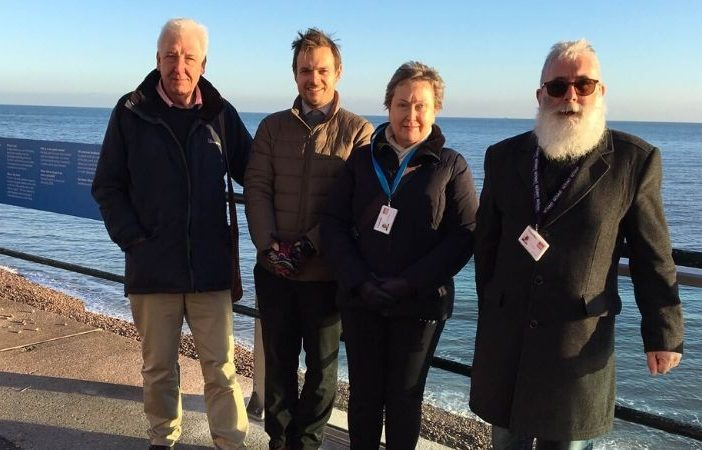 (l-r) Cllr Geoff Jung with East Devon's engineering projects manager and Cllrs Cathy Gardner and John Loudoun. They are standing next to the newly-installed glass test splash panel, which will be trialled in Sidmouth until the end of April.