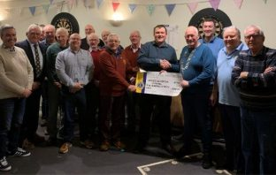 Members of Budleigh Salterton Lions Club present a cheque to Mike Hilliar of the carnival club.