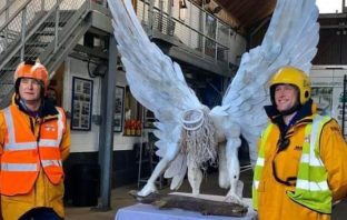 Exmouth RNLI crew members with the artwork. Picture: Jo Susans