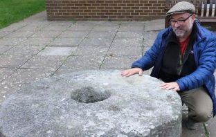 Roger Conant's descendant, Jeff Conant, a resident of California, with the mill stone outside the Church Hall, East Budleigh, during a 2016 visit to the UK. It is all that remains of his ancestors' mill, which was demolished in the early 20th century.