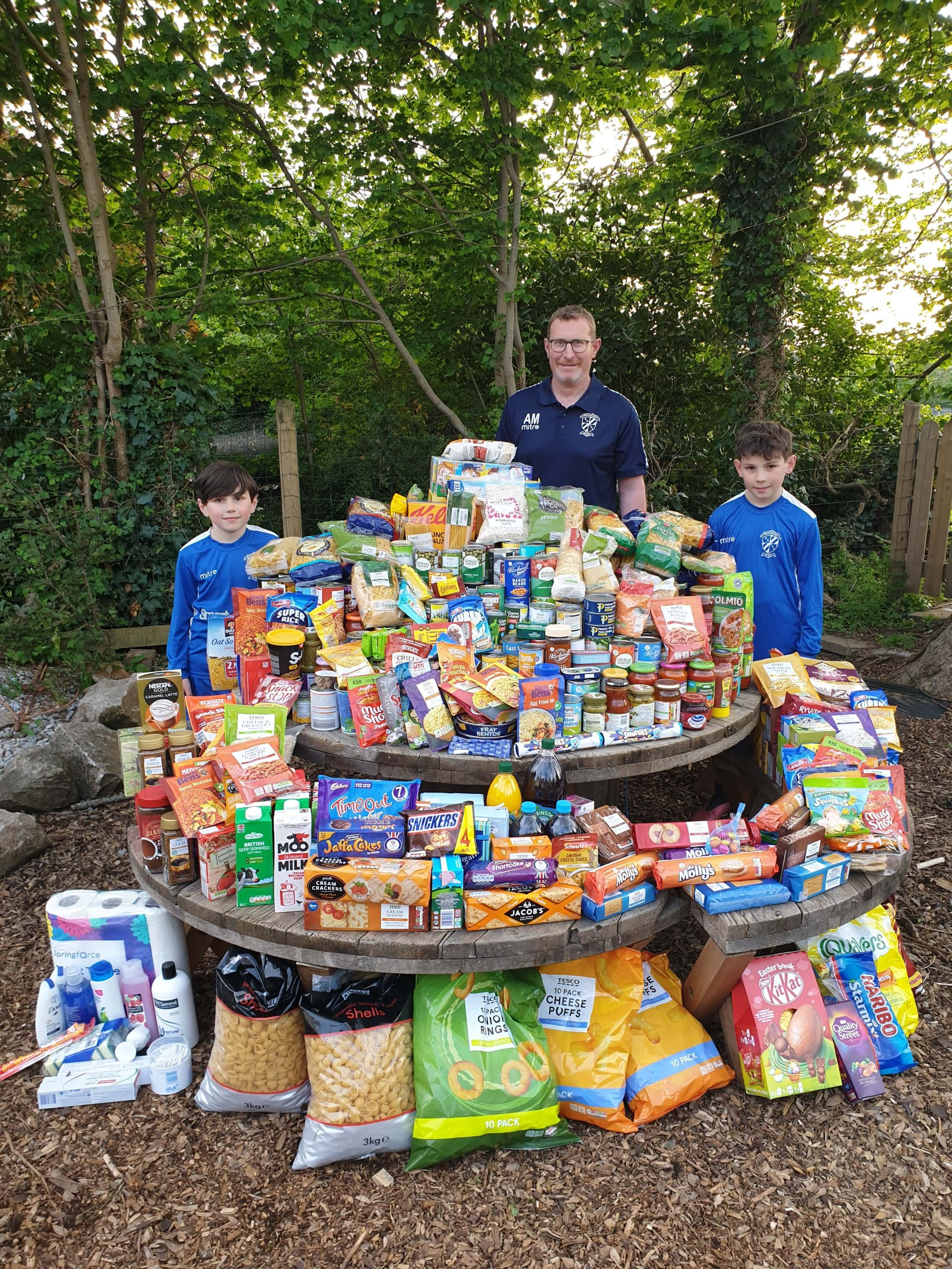 Brixington Blues under-14s coach Alan McBryan and two young players with the club's huge haul of food for Exmouth Community Larder.