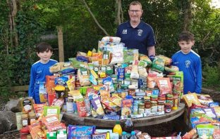 Exmouth Brixington Blues under-14s coach Alan McBryan and two young players with the club's huge haul of food for Exmouth Community Larder.