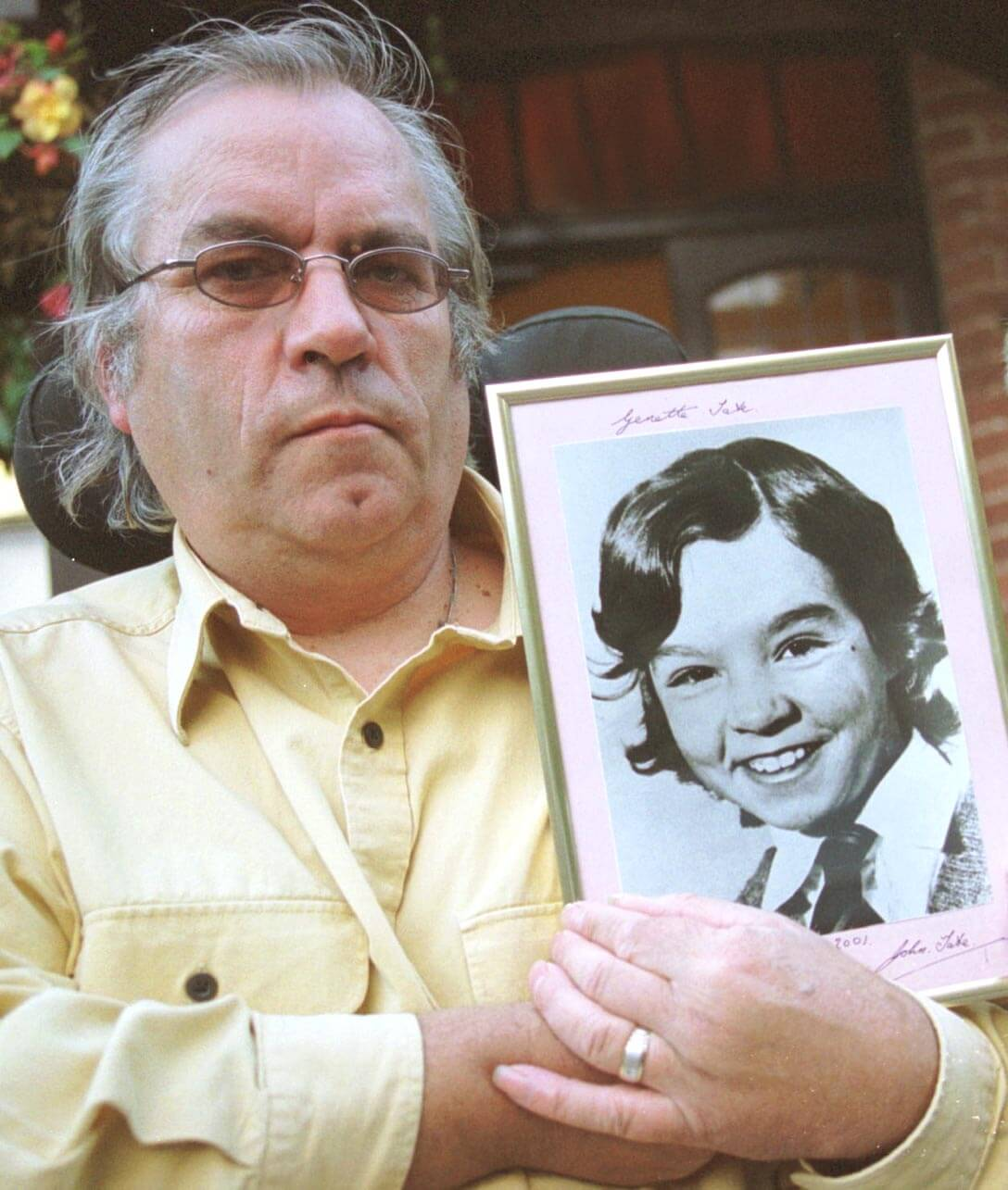 John Tate with a photo of his daughter Genette.