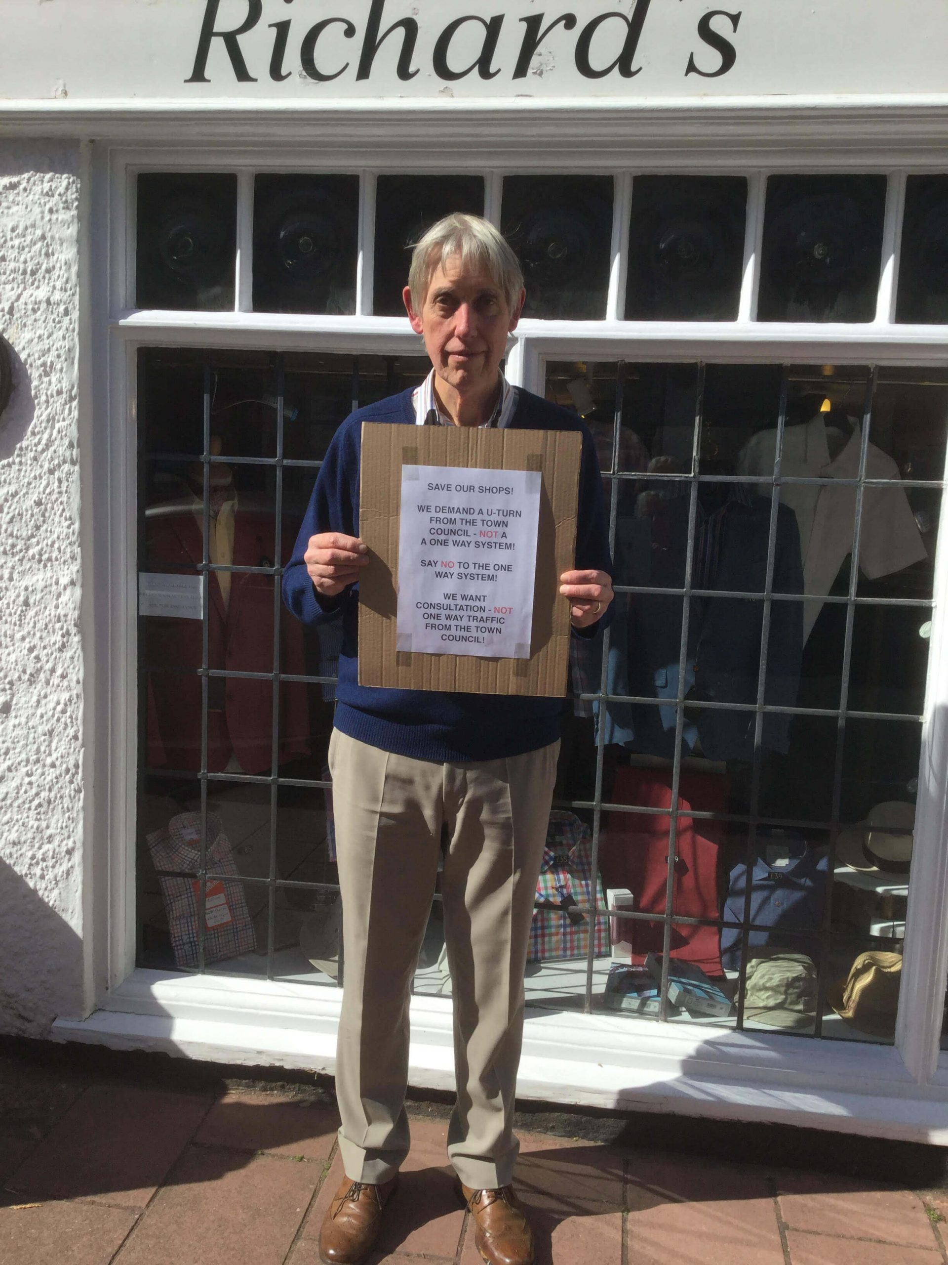 Budleigh Salterton business owner Richard Long with a poster highlighting the concerns of the majority of town's traders to a one-way system being introduced because of Covid-19 social distancing.
