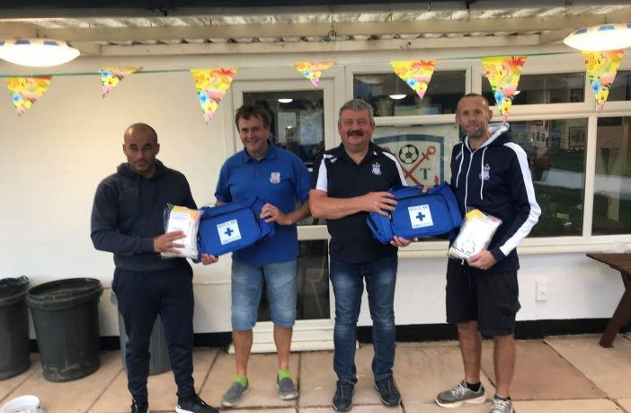 First-aid kits are presented to Exmouth Town FC youth team coaches Aaron Skinner and Martin Onoyiweta by Bill Edmunds and Jim Wallace from the supporters club.