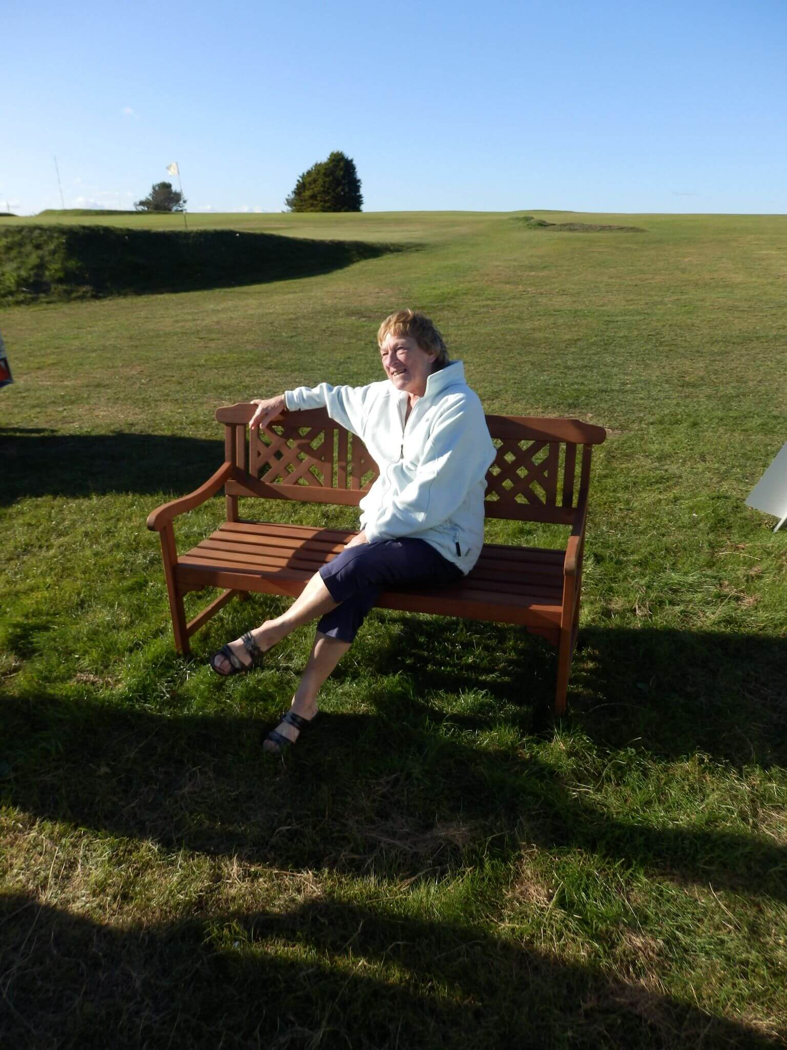 Mavis Motson, wife of the late Peter, sitting on the bench that the family have presented to the Axe Cliff Golf Club. picture: The Motson Family