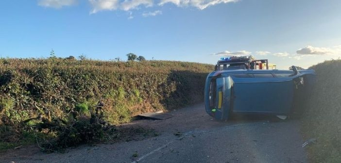 Firefighters rescue trapped man from an overturned car near Ottery St Mary