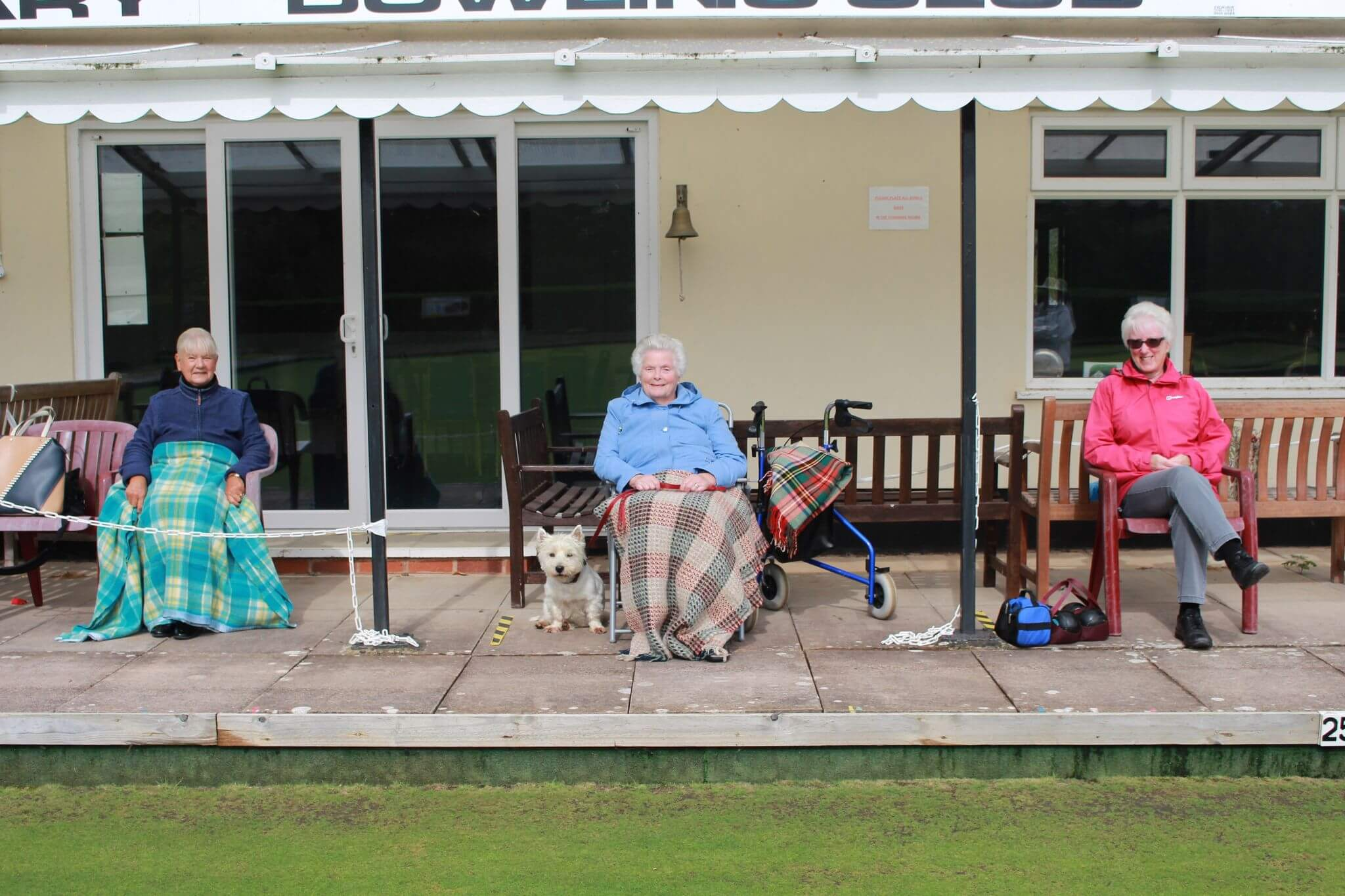 Socially distanced supporters taking in the action at Ottery St Mary Bowling Club.