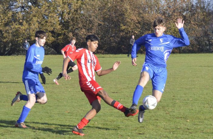 Brixington Blues U16s' Reece Alexander is challenged by a Budleigh player. Picture: Contributed