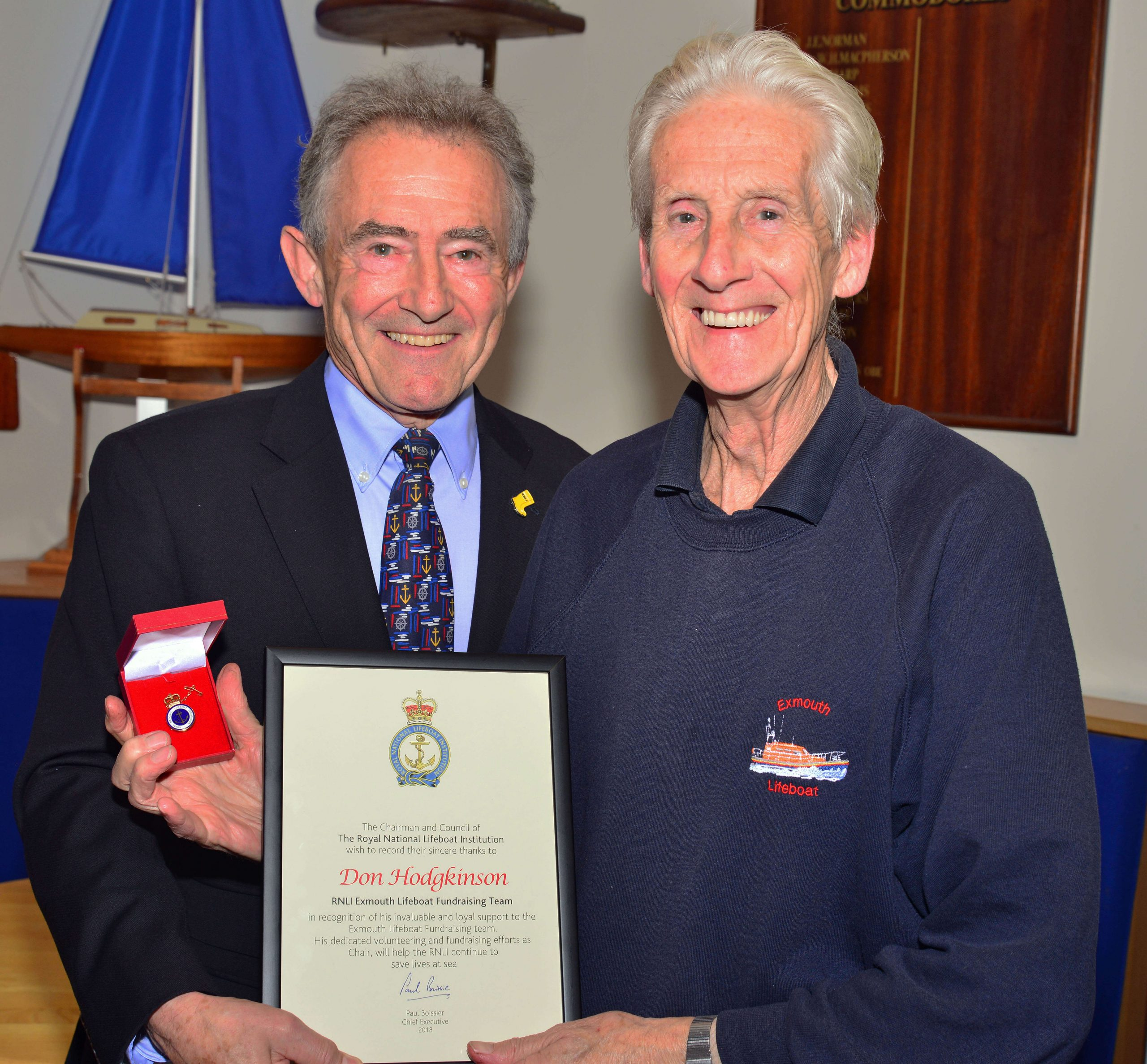 Exmouth RNLI volunteer Don Hodgkinson receiving his 20-year badge and certificate from former RNLI chairman Charles Hunter-Pease in 2018. Image: RNLI